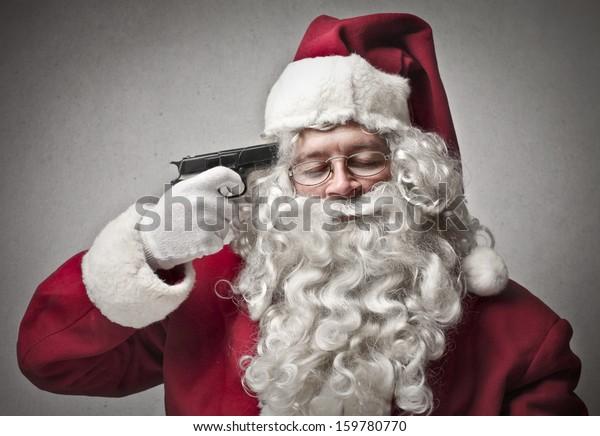 portrait of Santa Claus pointing a gun on his head