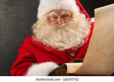 Portrait of Santa Claus reading big letter on old paper roll