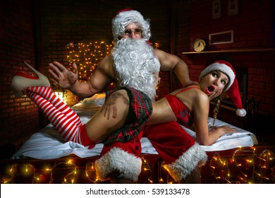 Portrait of Santa Claus sitting in the bed with sexy girl in Santa hats and slapping her