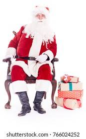 Portrait of Santa Claus sitting in chair with heap of Christmas gift boxes nearby, isolated on white