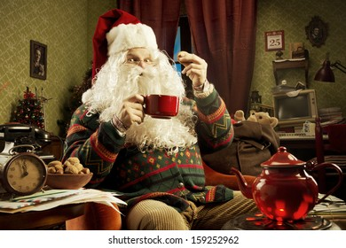 Portrait of Santa Claus sitting on armchair holding a cup of tea