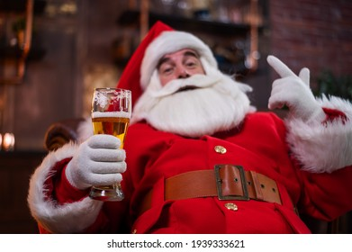 Portrait of santa claus sitting on a leather sofa and drinking beer for christmas