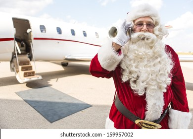Portrait of Santa Claus using mobile phone against private jet at airport terminal