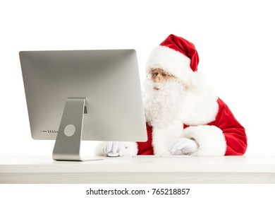 Portrait of Santa Claus working on computer isolated on white