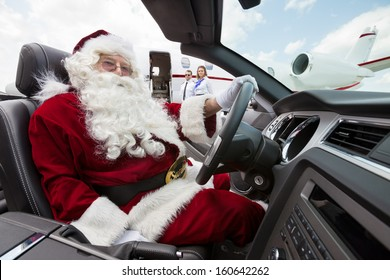 Portrait of Santa driving convertible with pilot and airhostess standing in background at airport terminal