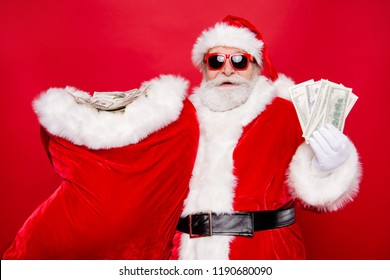 Portrait of Santa in eyeglasses gloves outfit holding carrying huge sack with currency discount sale lottery win winner congratulations isolated over bright vivid red background