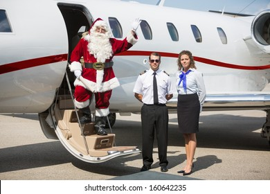 Portrait of Santa waving hand on private jet's ladder while pilot and airhostess standing by