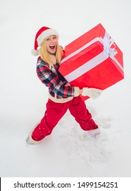 Portrait of Santa woman with huge red gift looking at camera. Christmas Woman holding a huge gift box. Lottery winner. Christmas winter people