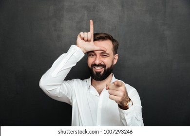 Portrait of sarcastic man showing loser sign on his forehead and pointing on camera with smile mocking or humiliate over graphite wall
