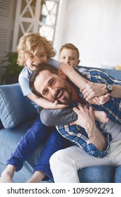 Portrait of satisfied bearded dad playing with little children. They sitting on sofa in living room. Optimistic kids and glad parent concept