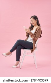 Portrait of a satisfied casual asian woman using mobile phone while sitting on a chair over pink background