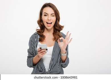Portrait of a satisfied casual girl holding mobile phone and showing ok gesture isolated over white background