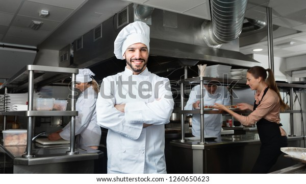 Portrait of satisfied cheerful positive  smiling chef on restaurant kitchen with busy professional staff