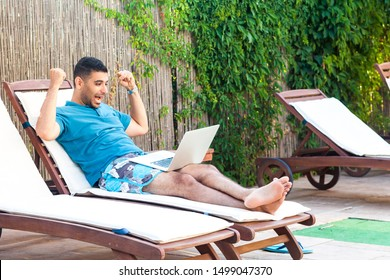 Portrait of satisfied handsome bearded young adult blogger man in blue t-shirt and shorts lying on cozy daybed with laptop on poolside and celebrate victory with raised arms. Lifestyle concept,outdoor
