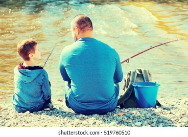 Portrait of satisfied happy friendly father and son fishing with rods in summer day