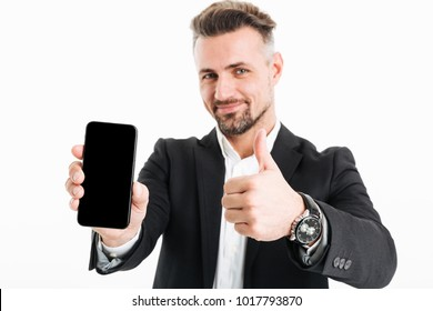 Portrait of a satisfied mature businessman dressed in suit showing blank screen mobile phone and giving thumbs up isolated over white background