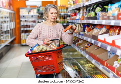 Portrait of satisfied mature woman with food products bought in the grocery shop