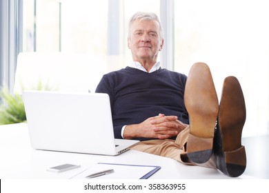 Portrait of satisfied senior businessman sitting at workplace in front of computer and looking at camera while relaxing. Old professional man feet on office desk.