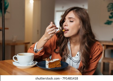 Portrait of a satisfied woman eating a piece of cake and drinking coffee while sitting at the table in a cafe indoors