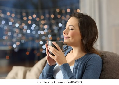 Portrait of a satisfied woman relaxing drinking coffee in the night sitting on a couch in the living room at home