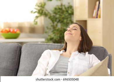 Portrait of a satisfied woman relaxing lying on a couch at home