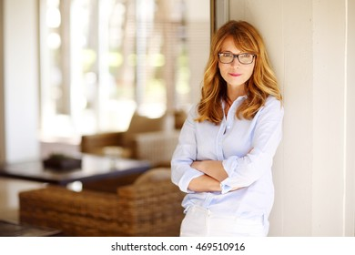 Portrait of a satisfied woman standing at home with arms crossed and smiling.