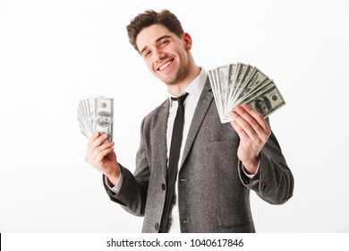 Portrait of a satisfied young businessman holding bunch of money banknotes isolated over white background