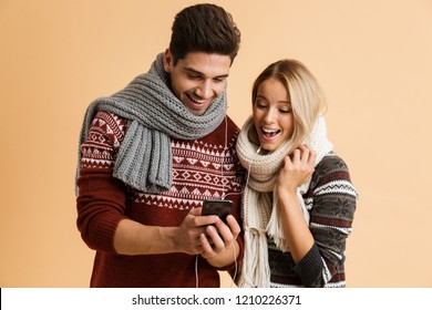 Portrait of a satisfied young couple dressed in sweaters and scarves standing together isolated over beige background, in earphones looking at mobile phone