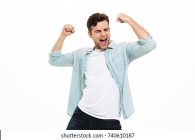 Portrait of a satisfied young man celebrating success isolated over white background