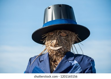 portrait of scarecrow with head in straw on blue sky background
