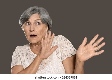 Portrait of a scared elderly woman on grey background