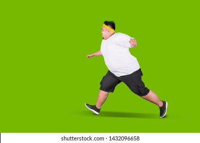 Portrait of a scared fat man running away from something in the studio with green screen
