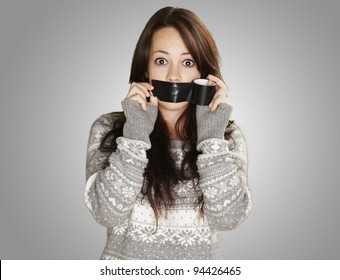 portrait of scared girl being silenced by herself over grey background