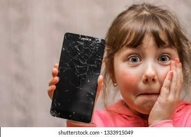 Portrait of a scared little girl with a broken mobile phone. A sad child broke the screen of a mobile phone. Cracked display in hand kids. The frightened child accidentally ruined the smartphone