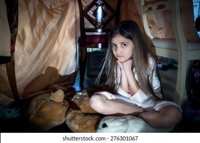 Portrait of scared little girl sitting on floor at creepy dark night