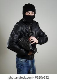 Portrait of scared male burglar with a handbag.