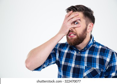 Portrait of a scared man covering his face with palm and looking at camera through fingers isolated on a white background
