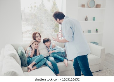 Portrait of scared mother with two kids sitting on sofa in modern living room afraid of violent angry father shouting gesturing with hands. Phychology upbringing concept