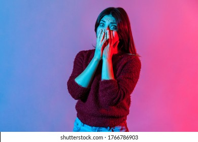 Portrait of scared panicked hysterical woman, covering her mouth with hands so not to scream with fear, looking frightened as notices something terrible. colorful neon light studio shot isolated