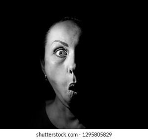 Portrait of a scared or surprised caucasian woman. Scary and fear concept. Black and white shot, low key lighting. Isolated on black.