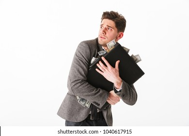 Portrait of a scared young businessman holding briefcase full of money banknotes isolated over white background