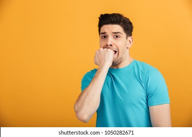 Portrait of a scared young man in t-shirt looking at camera isolated over yellow background