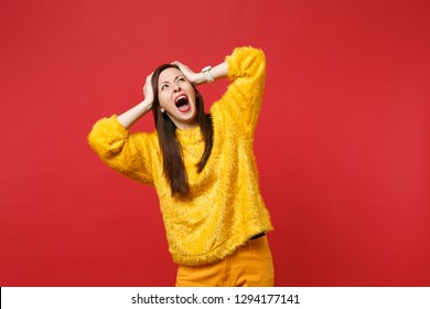 Portrait of scared young woman in yellow fur sweater screaming, looking up, clinging to head isolated on bright red background in studio. People sincere emotions lifestyle concept. Mock up copy space