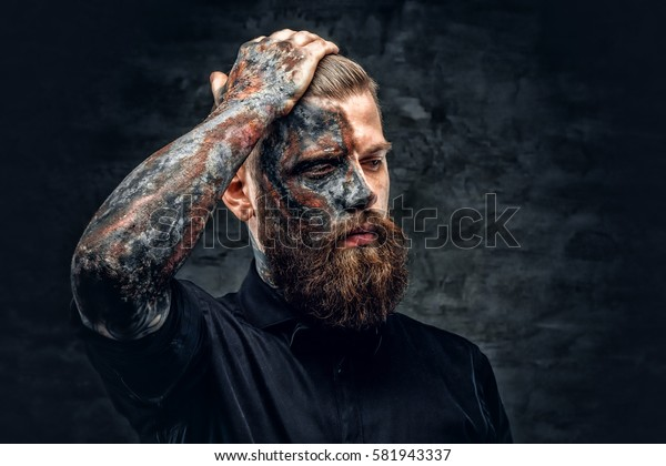 Portrait of a scary bearded male with burning make.