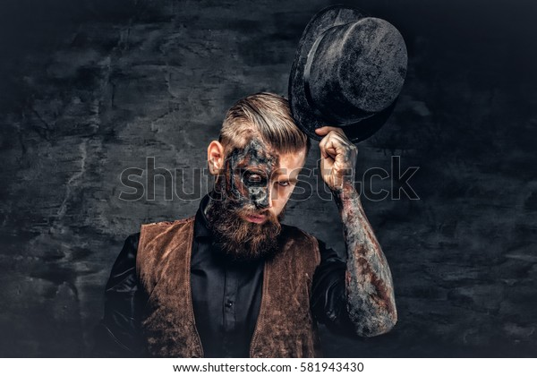 Portrait of a scary bearded male with burning make up and cylinder hat.