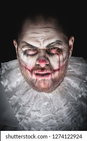 Portrait of a Scary Evil Clown.  Studio shot with horrible face art
