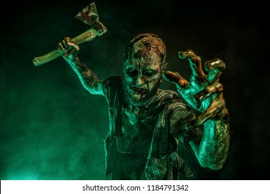 Portrait of a scary zombie with an axe. Halloween. Horror film.