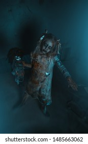 A portrait of scary zombie girl in room with a doll. Halloween. Horror film.