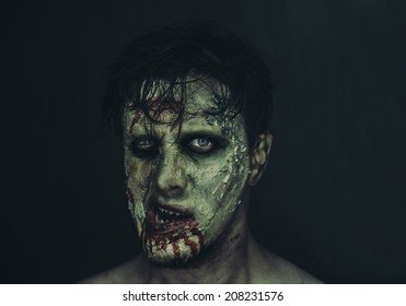 Portrait of scary zombie man on dark background, Halloween makeup