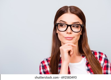 Portrait of sceptic young freelancer brown haired lady, she is in glasses, casual wear, on pure light background. So pensive and sexy